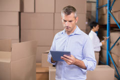 Warehouse manager using his tablet pc Royalty Free Stock Images