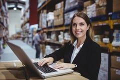 Warehouse manager using laptop Royalty Free Stock Image