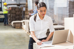 Warehouse manager using laptop and clipboard Stock Photos