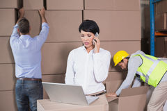 Warehouse manager using laptop and talking on phone Royalty Free Stock Photography
