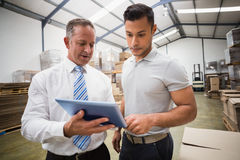 Warehouse manager using tablet pc with colleague. In a large warehouse Stock Photos