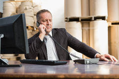 Warehouse manager using telephone and laptop Stock Photography