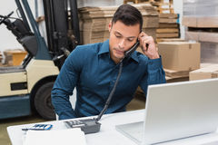 Warehouse manager using telephone and laptop Royalty Free Stock Photos