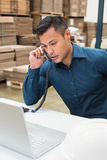 Warehouse manager using telephone and laptop Royalty Free Stock Image