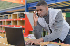 Warehouse manager using telephone and laptop in large warehouse. Warehouse manager using telephone and laptop in a large warehouse Stock Photo