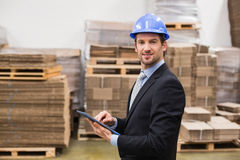 Warehouse manager wearing hard hat using tablet Royalty Free Stock Images