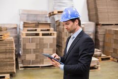 Warehouse manager wearing hard hat using tablet Stock Photo