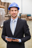 Warehouse manager wearing hard hat using tablet Stock Photography
