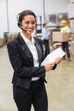 Warehouse manager wearing headset holding clipboard Stock Photos