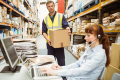 Warehouse manager wearing headset using laptop. In a large warehouse Royalty Free Stock Images