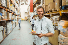 Warehouse manager wearing headset writing on clipboard. In a large warehouse Royalty Free Stock Photo