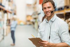 Warehouse manager wearing headset writing on clipboard Royalty Free Stock Photos