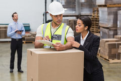 Warehouse manager and worker looking at clipboard Stock Photos