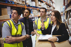 Warehouse manager and workers talking stock photos