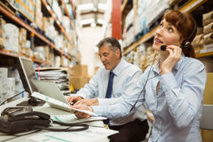 Warehouse manager working at her desk wearing headset Royalty Free Stock Photography