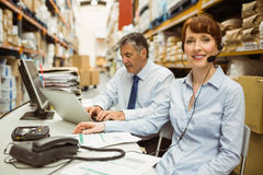 Warehouse manager working at her desk wearing headset Stock Image