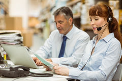 Warehouse manager working at her desk wearing headset Royalty Free Stock Images