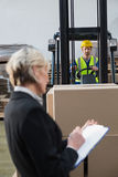 Warehouse manager writing on clipboard. In warehouse Stock Images