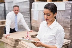 Warehouse manager writing on clipboard Royalty Free Stock Image