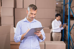 Warehouse manager writing on clipboard Stock Images