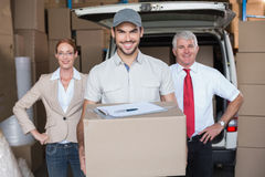 Warehouse managers and delivery driver smiling at camera Stock Photography