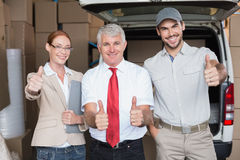 Warehouse managers and delivery driver smiling at camera Stock Photos