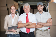 Warehouse managers and delivery driver smiling at camera Stock Images