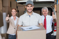 Warehouse managers and delivery driver smiling at camera Royalty Free Stock Image