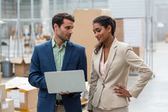 Warehouse managers discussing with the laptop. In warehouse Royalty Free Stock Image