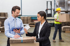 Warehouse managers holding box and looking at tablet pc Royalty Free Stock Photo