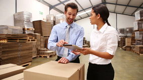 Warehouse managers looking at tablet pc stock footage