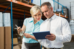 Warehouse managers looking at tablet pc. In a large warehouse Royalty Free Stock Images