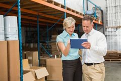 Warehouse managers looking at tablet pc Stock Photography