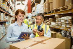 Warehouse managers looking at tablet pc. In a large warehouse Stock Photos