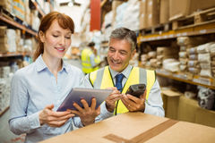 Warehouse managers looking at tablet pc. In a large warehouse Stock Photo