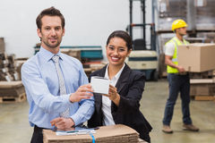 Warehouse managers showing box to camera Royalty Free Stock Images
