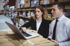 Warehouse managers using laptop Stock Photography