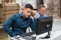 Warehouse managers using telephone and laptop Stock Photos
