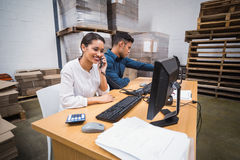Warehouse managers using telephone and laptop Stock Photography