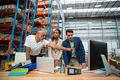 Warehouse managers and worker discussing with computer Stock Photos