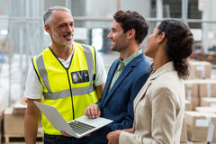 Warehouse managers and worker discussing with laptop. In warehouse office Stock Image