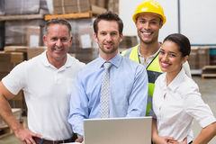 Warehouse managers and worker smiling at camera stock photography