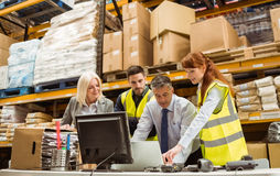 Warehouse managers and worker working on laptop. In a large warehouse Royalty Free Stock Photo