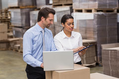 Warehouse managers working on laptop Royalty Free Stock Photos