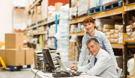 Warehouse managers working together on laptop Stock Photo