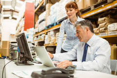 Warehouse managers working together on laptop Stock Image