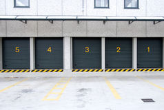 Warehouse - Mass storages. A line of four rental storage units with roll-up corrugated metal doors Stock Photo