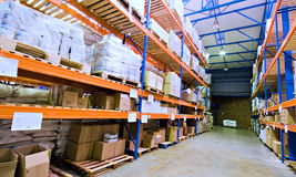 Warehouse and merchandise. Warehouse stacked with goods and merchandise on tall industrial shelves Royalty Free Stock Image