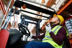 Warehouse Mover in Forklift. Side view portrait of young man sitting in forklift and using walkie-talkie while moving goods in warehouse, copy space stock image