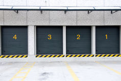 Warehouse - Numbered storages. A line of four rental storage units with roll-up corrugated metal doors Stock Photos